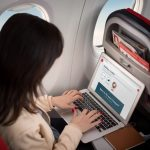 photo of woman with laptop on Norwegian flight